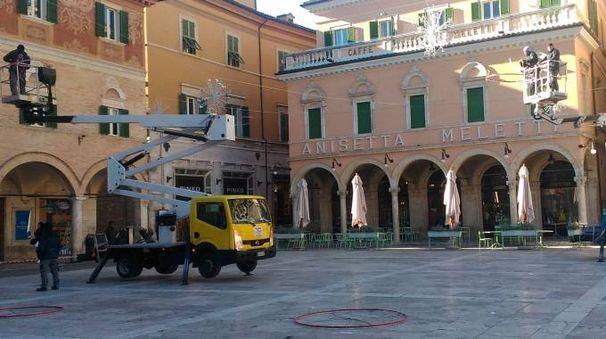 AL LAVORO Gli operi del comune sistemano  le luminarie in piazza del Popolo