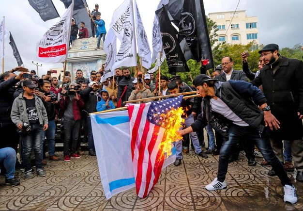 Manifestanti bruciano bandiera USA (foto AFP)