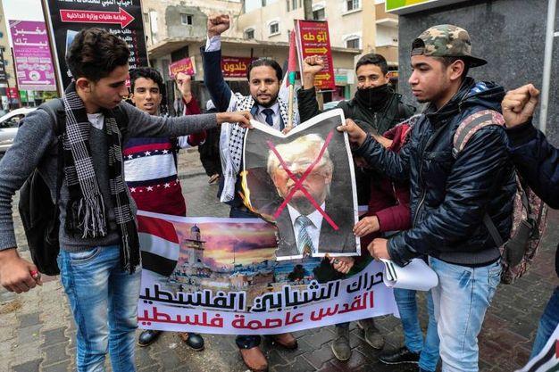 Giovani manifestanti nella striscia di Gaza protestano con effigi di Donald Trump (foto AFP)