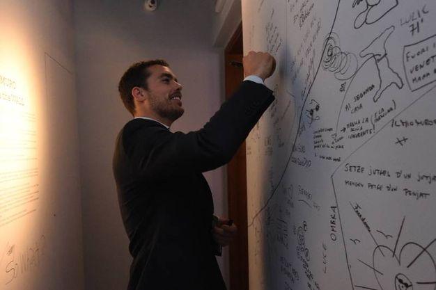 Alessandro Tommasi, public policy manager di Airbnb, lascia un messaggio sul muro durante il tour