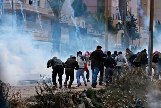 manifestanti palestinesi fuggono dal gas lacrimogene a Ramallah (AFP)