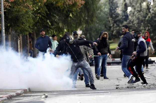 Manifestanti palestinesi con maschere anti-gas a Betlemme (Ansa)