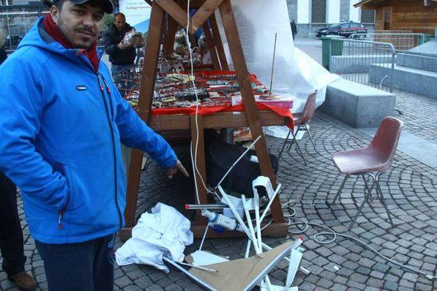 Un ambulante mostra la bancarella distrutta (Orlandi)