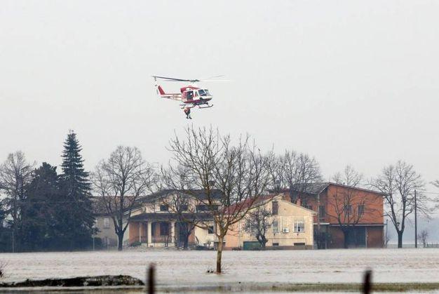 L'esondazione dell'Enza: elicottero dei Vigili del Fuoco salva persone sui tetti (Ansa)