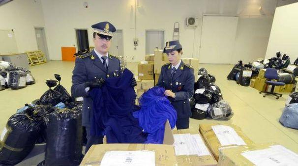 Gli agenti della Guardia di Finanza mostrano  i sacchi di abbigliamento sequestrato