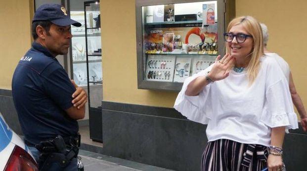 Marina Geirola con un agente fuori dalla sua gioielleria in giugno, dopo il furto di orologi