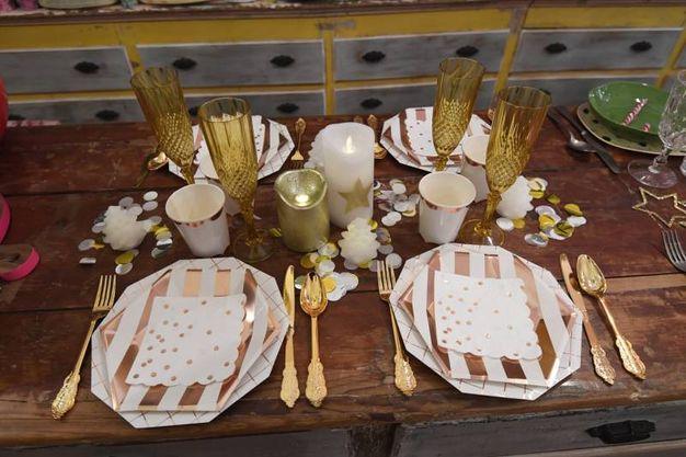Piatti di carta, bicchieri  di plastica  e candele. Il tocco 'in': stoviglie usa e getta dorate