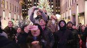 Turisti accanto all'albero del Rockefeller Center di New York (Afp)