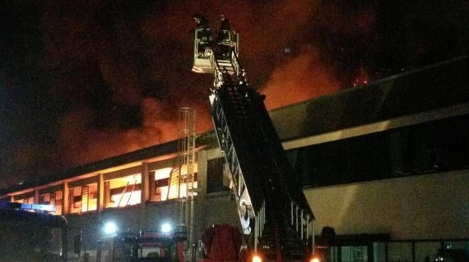 I vigili del fuoco in azione a Porcari, sull sfondo il capannone in fiamme