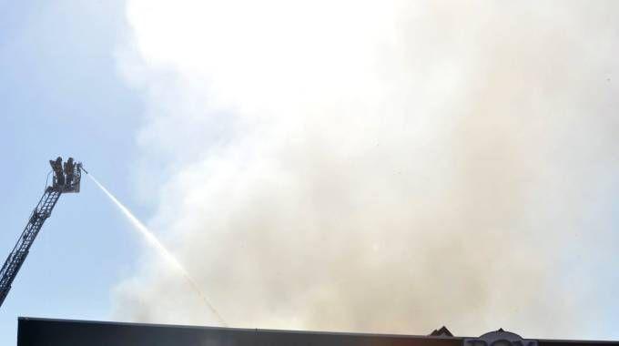 I vigili del fuoco al lavoro al capannone attaccato dalle fiamme (Foto Alcide)