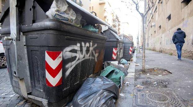 Un cassonetto pieno di rifiuti a Roma (Ansa)