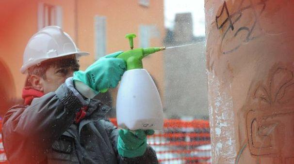 Un addetto pulisce i graffiti da uno dei portici del centro storico (FotoSchicchi)