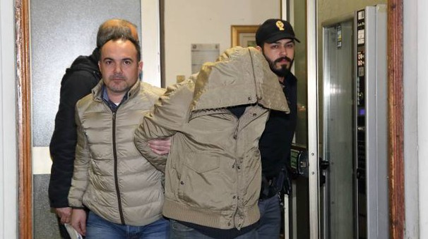 Uno degli arrestati mentre esce dal commissariato con la polizia