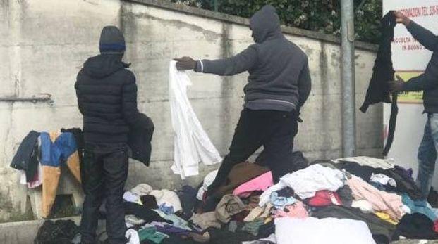 Alcuni migranti sorpresi a scegliere gli indumenti