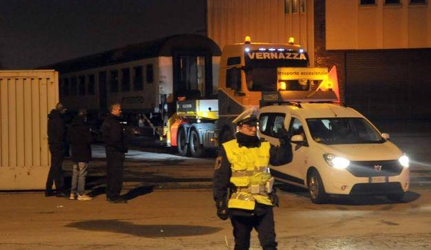 """I vagoni del treno deragliato caricati su tir e """"scortati"""" dalla polizia fino al deposito"""
