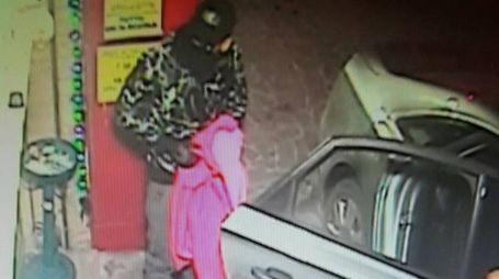 Uno dei banditi appena sceso dall'auto