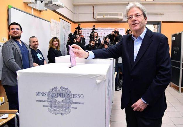 Gentiloni a Roma mentre infila la scheda nell'urna.  Secondo il ministero dovrebbe essere il presidente di seggio a compiere l'operazione (Ansa)
