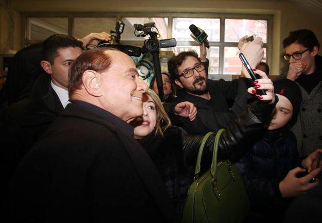 Silvio Berlusconi al voto a Milano, dove è stato contestato da una Femen a seno nudo (Lapresse)