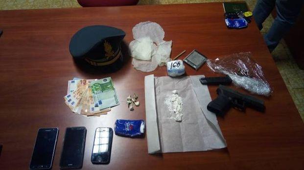 Lo stupefacente sequestrato dalla Finanza con i soldi e la pistola illegale anch'essi recuperati dai finanzieri
