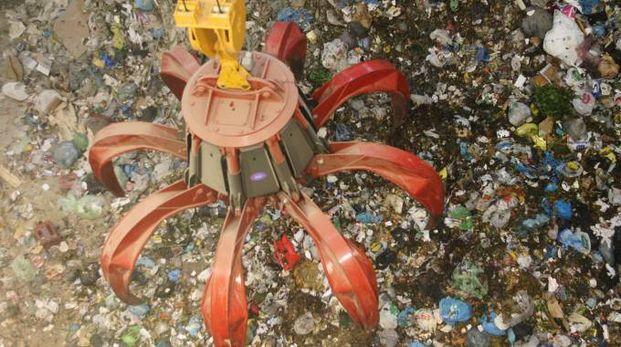Uno dei giganteschi 'ragni' utilizzati per smuovere le tonnellate di rifiuti (Isolapress)