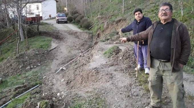 I fratelli Gerardo e Vito Grande mostrano la via che conduce a una delle loro case, letteralmente sprofondata