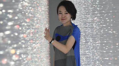 L'artista Hitomi Sato con la sua opera a 'The Wall'