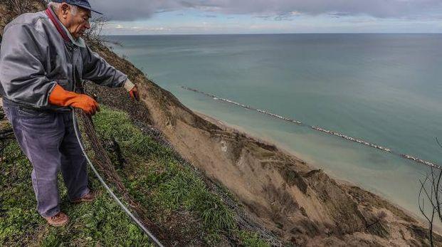 Un residente indica il vuoto lasciato sotto Fiorenzuola di Focara (Fotoprint)