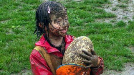 Una piccola atleta della scuola rugby sul terreno reso impraticabile dalla pioggia