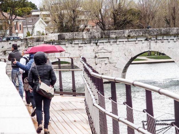 La prima passeggiata sotto la pioggia sulla nuova passerella del ponte di Tiberio (Foto Pasquale Bove)
