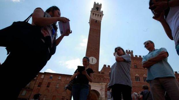 Turisti nel cuore di Siena in attesa di mettersi in cammino lungo i sentieri della via Francigena