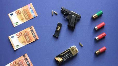 Pistola, soldi falsi e munizioni
