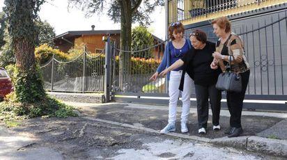 Alcune residenti in via Val d'Ossola indicano i punti in cui la strada è danneggiata