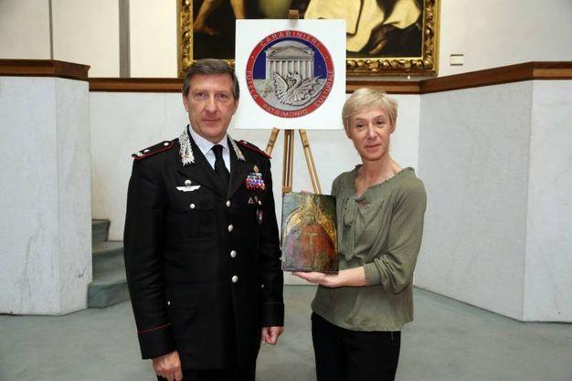Il generale Parrulli e Elena Rossoni direttrice Pinacoteca Nazionale di Bologna mostrano il Sant'Amborgio ritrovato (Foto Schicchi)