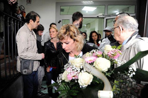 La mamma di Pamela esce dall'obitorio stringendo i fiori di Traini (foto Calavita)