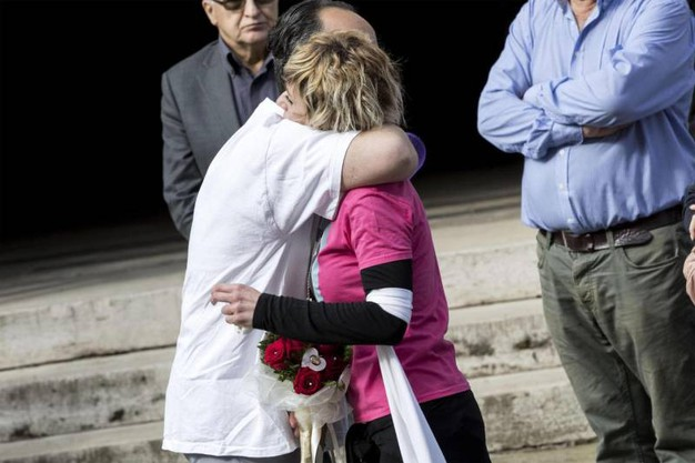 La mamma di Pamela con la maglietta rosa e in mano un mazzo di rose rosse (Foto Ansa)