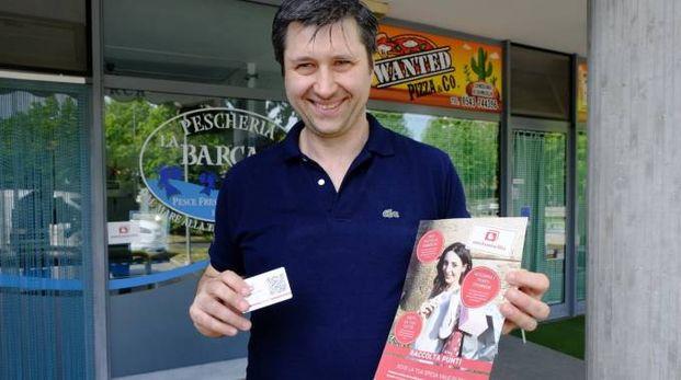 Luca Arrigoni con la fidelity card che garantisce punti ai clienti di negozi e botteghe convenzionato (Frasca)