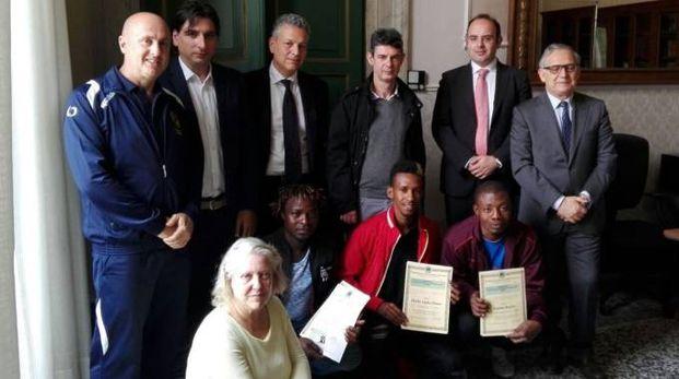 Enrico Ricci e Manuela Bondielli con i tre giovani migranti che hanno in mano il brevetto