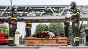 Sulla bara l'elmetto nero da pompiere con su scritto il nome, poi la cintura rossa di protezione con attaccato il moschettone e una corona di rose e gigli dei colori della sua Alma (Fotoprint)