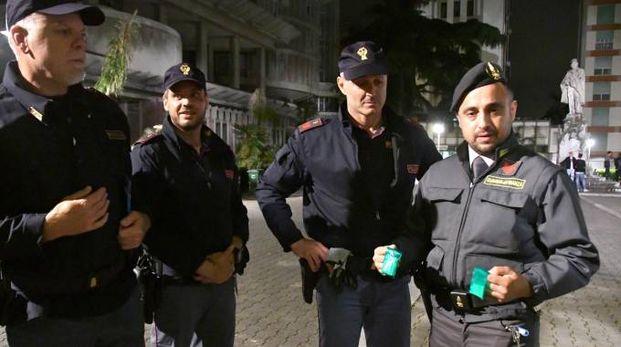 Poliziotti e finanzieri mostrano la droga trovata in un'aiuola del viale Chiesa (foto Paola Nizza)