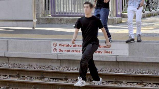 Un giovane attraversa i binari in stazione a Trezzano