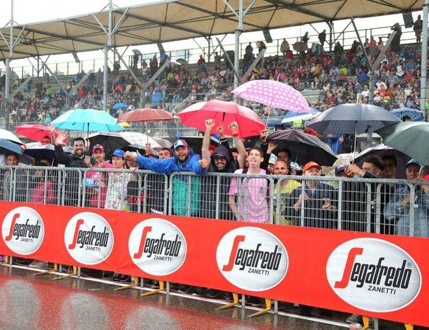 L'attesa sotto l'ombrello (foto Isolapress)