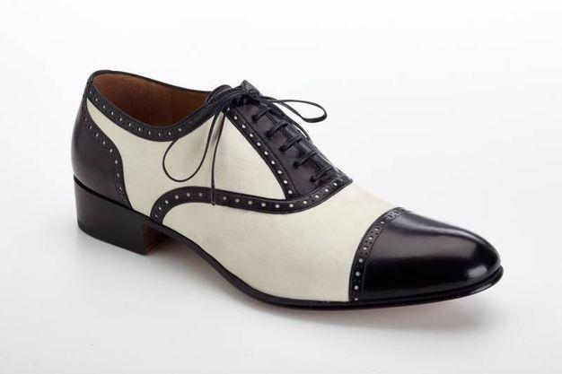 Rodolfo Valentino ha scelto e indossato questo elegante modello di scarpa allacciata bicolore firmata Salvatore Ferragamo. Oxford bimateriale in vitello e nabuk nei colori nero e magnolia con perforazione regolare lungo i bordi. Tacco 3 cm