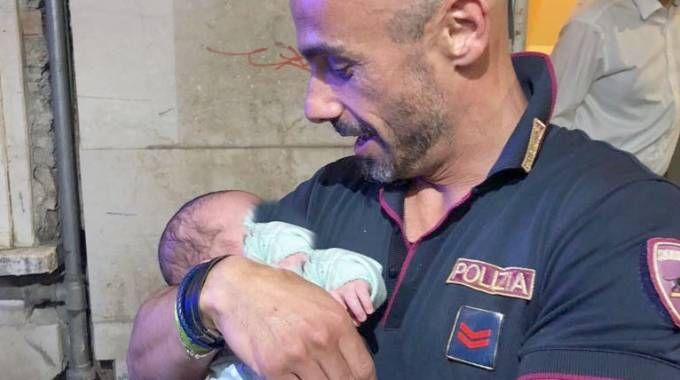 Il neonato in braccio a un agente di polizia (Lapresse)