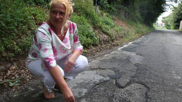 Una residente in un punto dove la pavimentazione è più dissestata