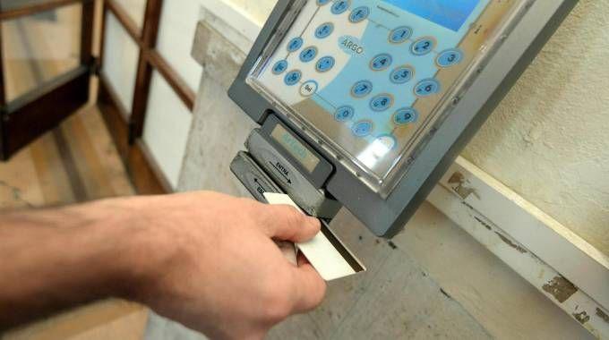 Un dipendente mentre timbra il cartellino (Foto d'archivio)