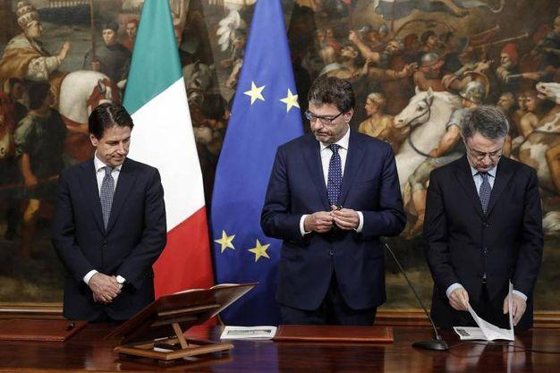 Giuseppe Conte, Giancarlo Giorgetti (senza la spilla di Alberto da Giussano) durante il giuramento (Ansa)
