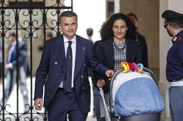 Il sottosegretario ai Trasporti Edoardo Rixi lascia Palazzo Chigi al termine del giuramento dei neo sottosegretari accompagnato dalla moglie Marzia Vitacon bebè al seguito (Ansa)