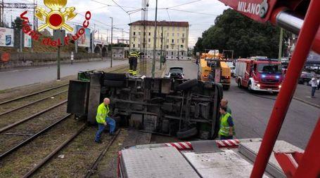 Il camion Amsa ribaltato sui binari del tram