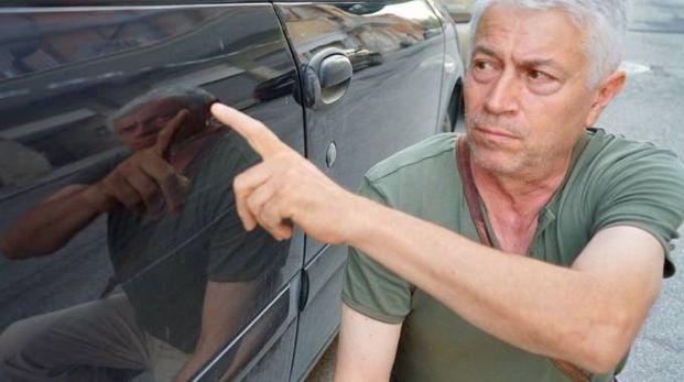 Angelo Fonti, 60 anni, titolare del Bar Stadio  di Civitanova, mostra gli sfregi sulla sua Fiat Multipla (foto De Marco)