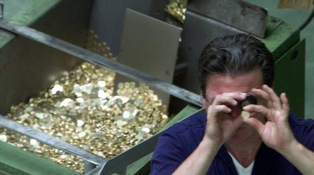 Un tecnico della Zecca esamina le monete coniate (foto Ansa)